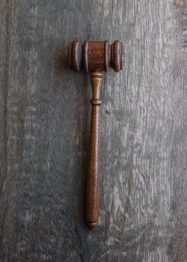 Worn wooden gavel resting on a wood surface.